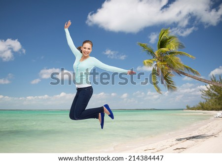 summer vacation, travel, tourism, freedom and people concept - smiling young woman jumping in air over tropical beach background