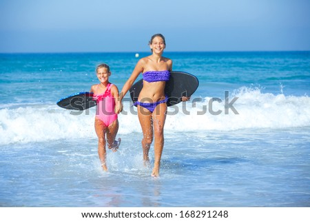 Summer vacation - Two cute girls in bikini with surfboard running from the ocean.