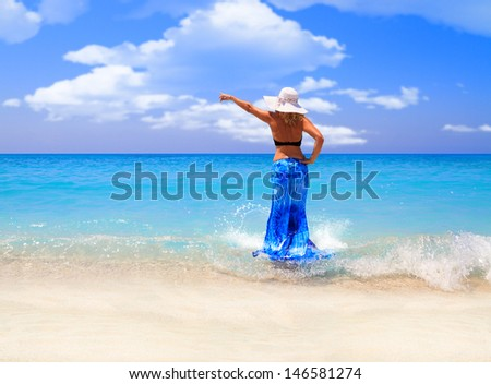 Summer vacation woman on the beach in beach hat enjoying summer holidays looking at the ocean - stock photo