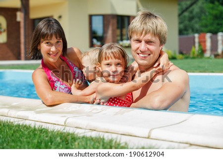 Summer vacations concept. Happy family with two kids playing in blue water of swimming pool. - stock photo