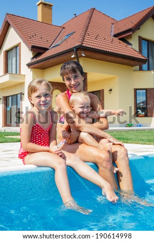 Summer vacations concept. Happy mother and daughters playing in blue water of swimming pool.