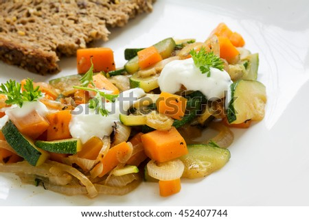 summer vegetables from zucchini and carrots with soured cream, parsley garnish and whole grain bread, a light and healthy dish on a white plate, closeup with selected focus and narrow depth of field - stock photo