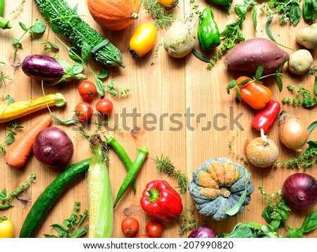 Summer vegetables with herbs on wooden background