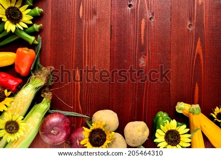Summer vegetables with sun flowers on brown wooden background.