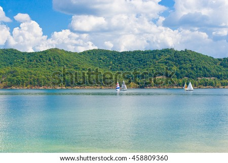 Summer view of a local lake with sailboats and beautiful  forest on  lake hillside shore in Kentucky, USA - stock photo
