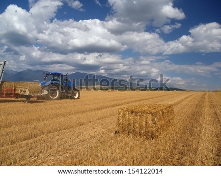 Summer view of harvested wheat field with blue tractor collecting packed crops of hay in Liptov region, central Slovakia. In the distance can be seen peaks of Rohace mountains, the Western Tatras.