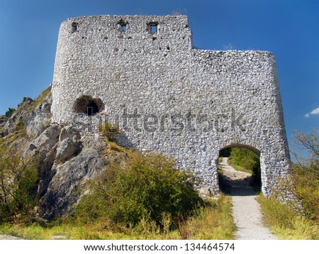Summer view of massive fortification ruins of Castle of Cachtice situated in mountains above the Cachtice village in the west of Slovakia in Trencin region. - stock photo