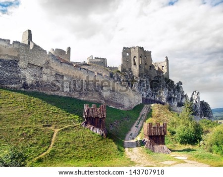 Summer view of ruined castle of Beckov surrounded by massive fortification. The Castle of Beckov is situated in village Beckov, Trencin region, the western Slovakia. - stock photo