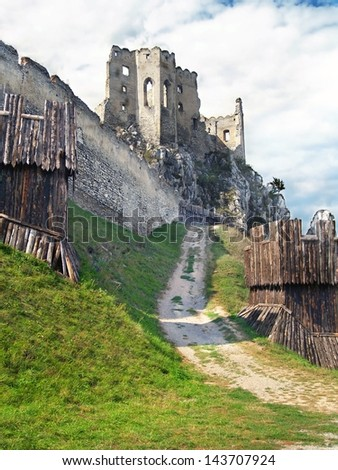 Summer view of ruined castle of Beckov with massive fortification and ruined chappel in background. The Castle of Beckov is situated in village Beckov, Trencin region, western Slovakia. - stock photo