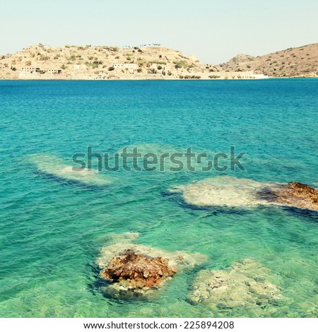 Summer view of Spinalonga island, a Venetian fortress and leper colony, in beautiful Mirabello Gulf, Aegean sea(Crete, Greece). square toned image, instagram effect - stock photo