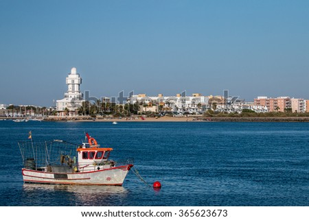 Summer view of the calm waters with sail boat and blue sky near Isla Cristina, Spain.