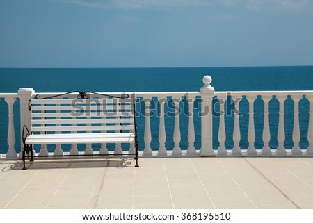 Summer view with classic white balustrade, bench and empty terrace overlooking the sea, selective focus - stock photo