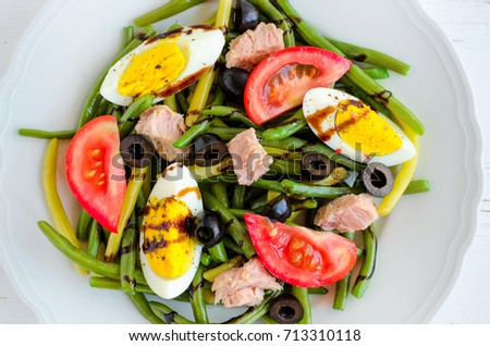 Summer warm salad with cooked green beans, tuna, tomatoes, boiled eggs and sauce balsamico glassa in white plate on wooden background. Healthy eating concept. Top view.