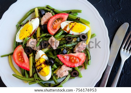 Summer warm salad with cooked green beans, tuna, tomatoes, boiled eggs and sauce balsamico glassa in white plate with knife and fork on black stone background. Healthy eating concept. Top view.
