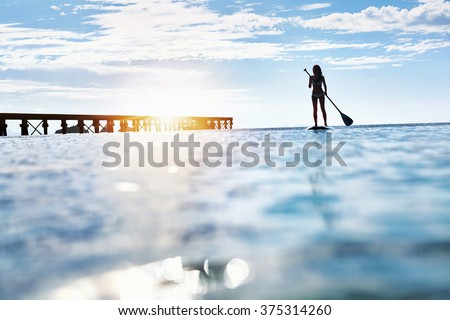Summer Water Sports. Silhouette Of Free Fit Woman Paddling, Stand Up On Paddle, Surf Board In Sea. Holidays Travel Vacation. Healthy Lifestyle. Recreation. Leisure Activity. Freedom, Wellness Concept - stock photo