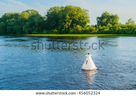 Summer water sunset landscape - green trees along the bank of the river and buoy on the water under warm sunset light. Summer landscape nature. - stock photo