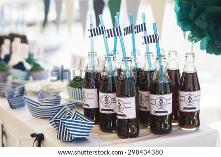 Summer wedding decoration for party. Hand made sweets. Served banquet table, macaroons and cupcakes. Bottles of cola soda. Sea style. - stock photo