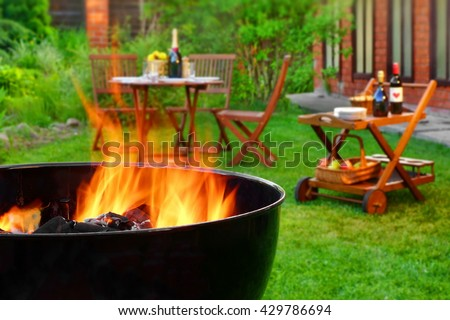 Summer Weekend BBQ Scene On The Backyard. Flaming Charcoal Grill Close Up. Outdoor Wooden Furniture  On The Blurred Background. - stock photo