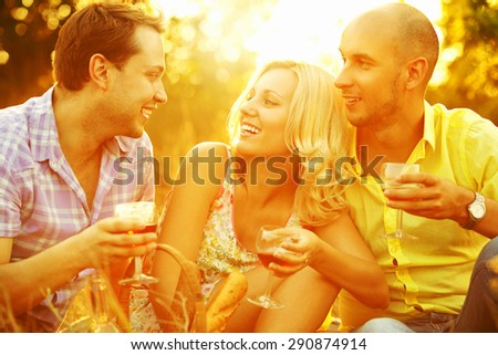 Summer weekend concept. Portrait of happy group of friends in trendy casual clothing drinking red wine, talking and having fun. Sunny autumn day. Outdoor shot