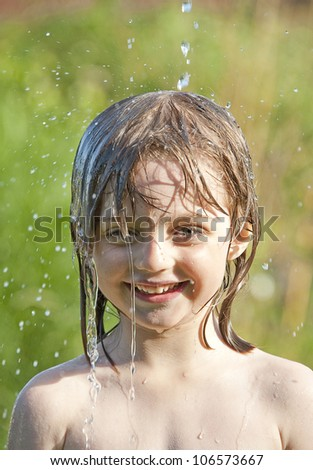 summer wet portrait of little girl playing with water