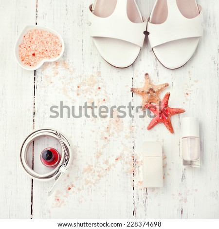 Summer white and coral women's accessories - sandals, nail polish, belt, perfume bottle, bath salt, on wooden floor. White collection. Marine style fashion, beach holiday, skincare, shopping concepts. - stock photo