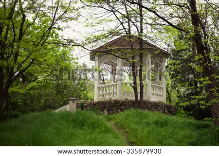 Summer white gazebo in a wooded park - stock photo