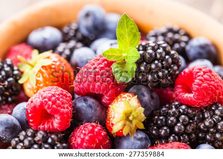 Summer wild berries over shabby wooden  background. Raspberry, strawberry, blackberry and blueberry in a bowl - stock photo