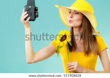 Summer woman wearing yellow dress and hat with sunflower taking self picture with old vintage camera on blue background