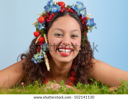 Summer woman with strawberries, fruit and flowers in her hair lying in green grass - stock photo