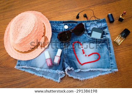 Summer women's accessories: red sunglasses, beads, denim shorts, mobile phone, headphones, a sun hat, nail polish, open lipstick, perfum. Toned image  - stock photo