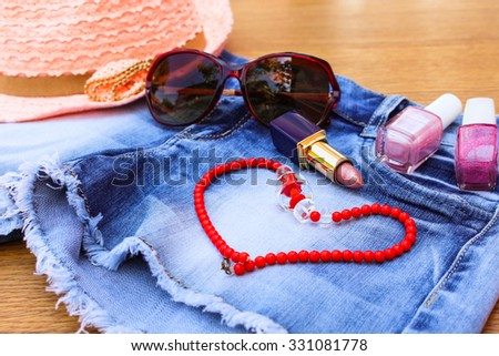 Summer women's accessories: sunglasses red, beads, denim shorts, sun hat, nail polish, lipstick open.   - stock photo