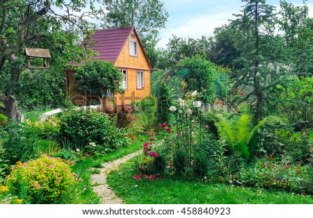 Summer wooden house on background of green garden,  landscape.