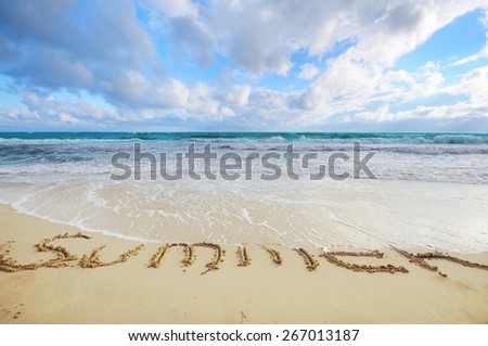 Summer word written on sand being washed out with tide