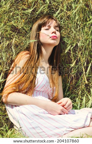 summer young woman  in hay of dry grass - stock photo