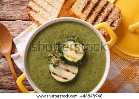 Summer Zucchini soup close-up in yellow saucepan and toast on the table. Horizontal view from above
