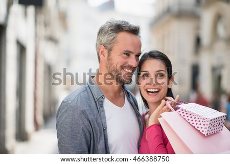 Summertime. A trendy couple walking on the streets, the grey haired man holding a mug of coffee and the brunette woman has shopping bags on her shoulder