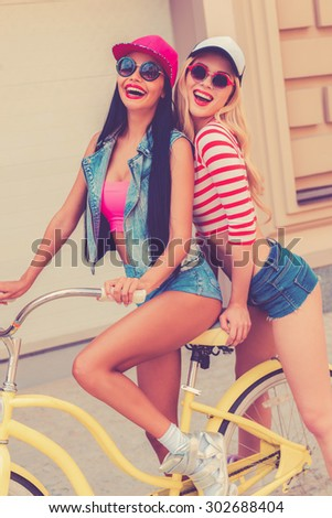 Summertime is fun time. Cheerful young woman sitting on bicycle while her female friend standing behind her - stock photo