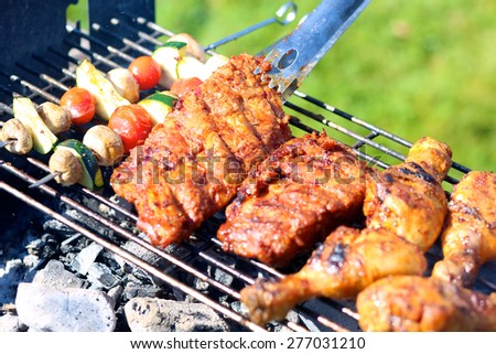 Summertime meal: assorted meat and vegetables on barbecue grill cooked for summer family dinner - stock photo