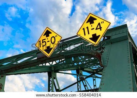Summertime shot of an old green iron bridge in Vermont with the clearance signs in feet on yellow diamond street signs