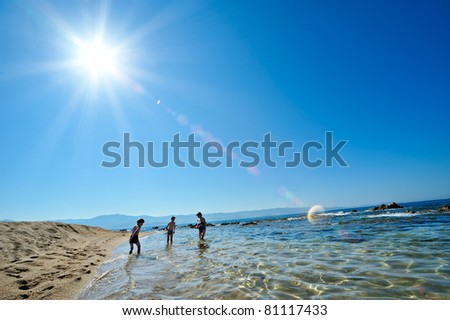 summertime - two boys and their mother playing on the beach