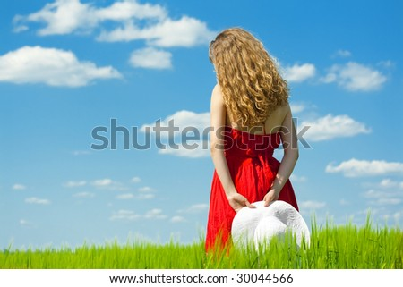 summertime; woman in red dress standing on green field over blue sky - stock photo