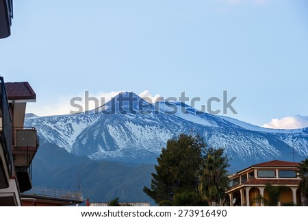 Summit of Mount Etna, active volcano in Sicily, Italy, spewing ash and gasses from its two erupting craters, photographed from the foothill town. Travel destination and forces of nature concept.  - stock photo
