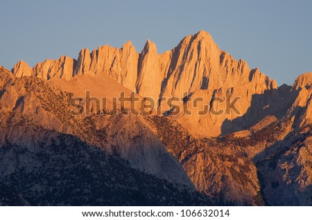 summit of Mount Whitney the highest mountain in the contiguous United States lit up by morning sunrise - stock photo