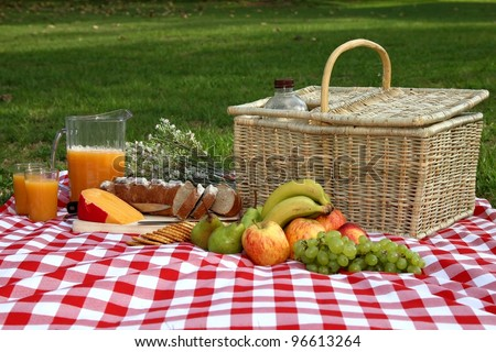 Sumptuous picnic spread out on a red and white checked cloth with wicker basket - stock photo