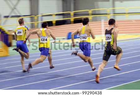 SUMY, UKRAINE - FEB.17: Unidentified men on the finish of the 60 meters dash during the Ukrainian Track and Field Championships on February 17, 2012 in Sumy, Ukraine. - stock photo