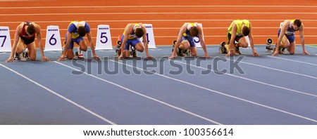 SUMY,UKRAINE-FEB.16: Unidentified men on the start of the 60 meters dash during the Ukrainian Track and Field Championships on February 16, 2012 in Sumy, Ukraine. - stock photo