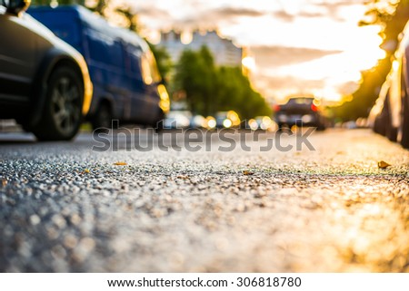Sun after the rain in the city, driving cars, view from the road level - stock photo