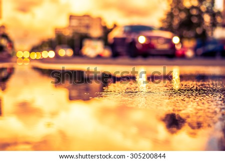 Sun after the rain in the city, view of the approaching car with a level of puddles on the pavement. Image in the yellow-purple toning - stock photo