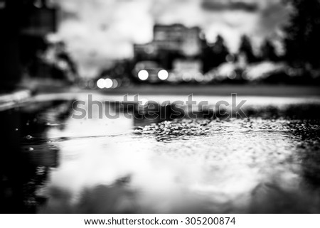 Sun after the rain in the city, view of the approaching car with a level of puddles on the pavement. Image vignetting and black and white tones - stock photo