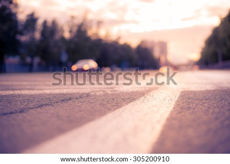 Sun after the rain in the city, view of the approaching car with the level dividing line. Image in the soft orange-purple toning - stock photo